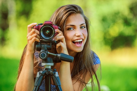 Portrait of young beautiful woman photographed with camera tripod, on green background summer nature. Stock Photo