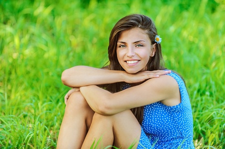 outdoor glamour: Portrait of young beautiful woman sitting on grass and smiling, on green background summer nature.