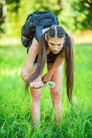 field glass: Portrait of young beautiful woman wearing backpack and looking bugs through magnifying glass, on green background summer nature. Stock Photo