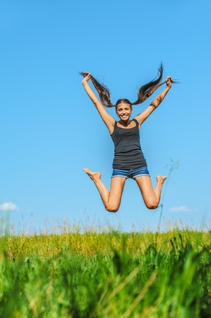 Portrait of young beautiful woman jumps high into sky, on green background summer nature. photo