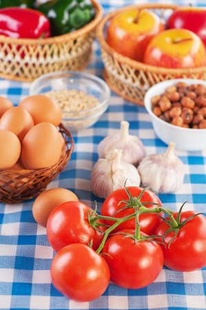 viands: Ingredients for breakfast: tomatoes, eggs, garlic, peanuts, apples and lettuce. Stock Photo
