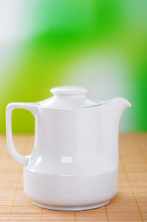 viands: White small jug of milk costs on bamboo table cloth, on a background of green summer garden.