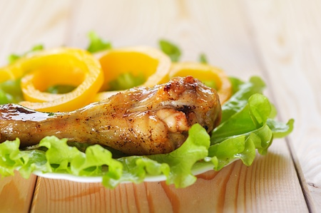 viands: Fried chicken drumstick with green leaf lettuce and yellow bell peppers on a rustic wooden table. Stock Photo