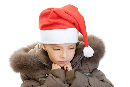 orchestration: Beautiful little girl in warm winter jacket and red Christmas hat sad, isolated on white background.