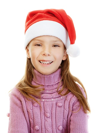 Beautiful little girl in pink sweater and red Christmas hat smiles, isolated on white background. photo