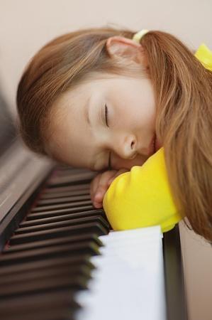 Beautiful little girl in yellow dress asleep on piano. photo