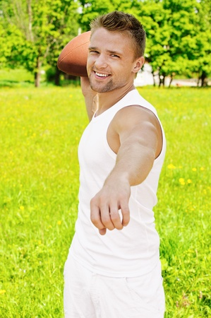 hurl: Portrait of beautiful young dressed in white sportsman with rugby ball, against green of summer park. Stock Photo