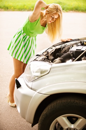 car exhaust: Nice young woman repairing car, against green of summer park.