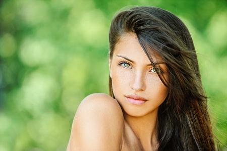 earnest: Retrato de joven bella mujer con los hombros desnudos, en la naturaleza verde de verano, de fondo.