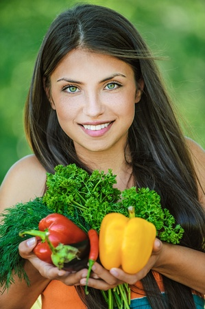 viands: Portrait of young beautiful woman with bare shoulders holding a vegetable - parsley, pepper, eggplant, on green background summer nature. Stock Photo