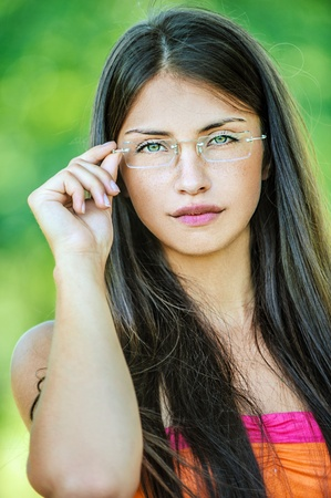 Portrait of young beautiful woman adjusts glasses, on green background summer nature. Stock Photo - 13589435