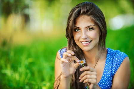 fortunetelling: Portrait of young beautiful woman wonders, tearing petals on daisy, on green background summer nature. Stock Photo