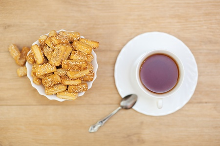 strew: Bread sticks sprinkled with sesame seeds and cup of tea on wooden table.
