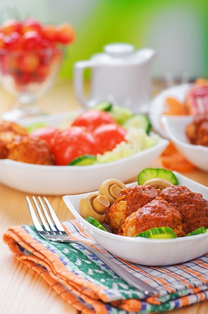 viands: Meat cutlets with cucumber and mushrooms in a bowl on dining table, on background of green summer garden.