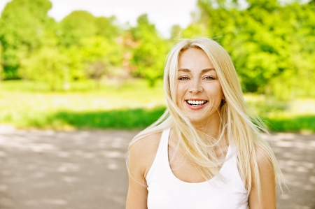 Charming young woman laughs merrily dressed in white, against green of summer park. Stock Photo - 13636838