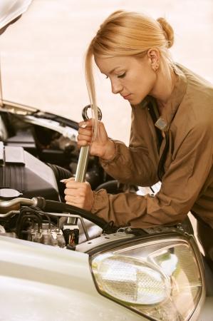 Mooie jonge vrouw reparatie van auto, tegen groen van de zomer park. Stockfoto