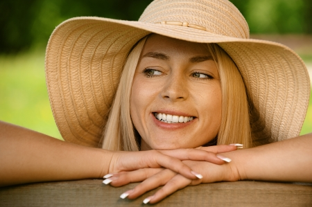 Pretty smiling young woman in hat sitting on wooden bench close up, against green of summer park. photo