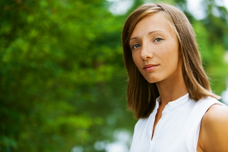 Portrait of beautiful young woman, against green of summer park. Stock Photo - 13636749