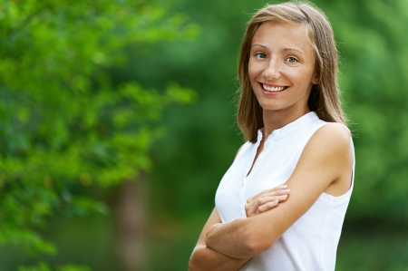 sprightly: Portrait of smiling beautiful young woman, against green of summer park. Stock Photo
