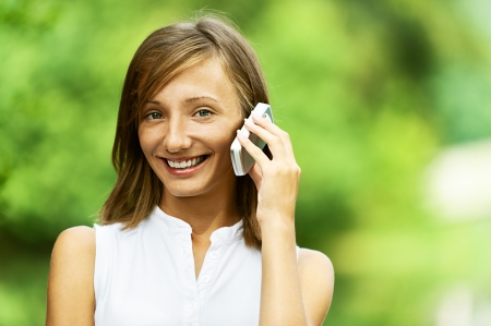 Pretty young woman talking on cell phone, against green of summer park. photo