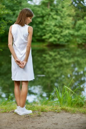 Portrait of beautiful young woman back near lake, against green of summer park. Stock Photo - 13636763
