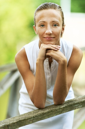 leaned: Portrait of beautiful young woman leaned on wooden railing, against green of summer park.