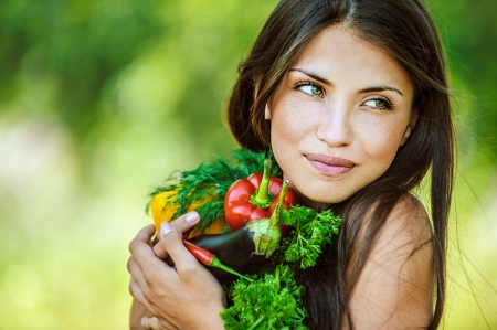 bare shoulders: Portrait of young beautiful woman with bare shoulders holding a vegetable - parsley, pepper, eggplant, on green background summer nature. Stock Photo
