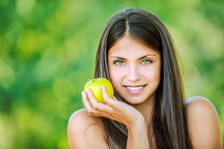 Portrait of young beautiful woman with bare shoulders holding an apple and smiling, on green background summer nature. photo