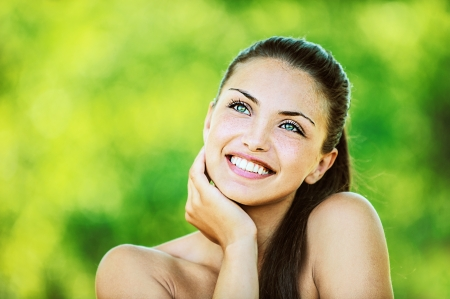 Portrait of young beautiful woman with bare shoulders laughs and looks up and smiling, on green background summer nature.