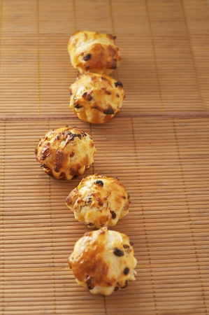 viands: Small muffins on bamboo table cloth.