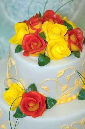 the trappings: Luxurious large cake decorated with cream yellow and red flowers. Stock Photo
