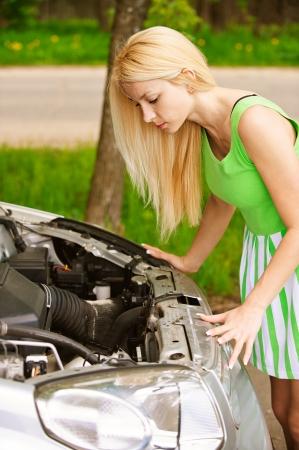 breakdown: Nice young woman repairing car, against green of summer park.