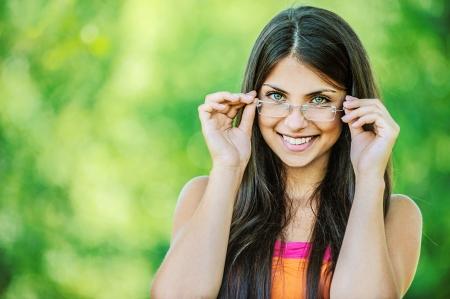 Portret van jonge mooie vrouw past een bril en glimlachend, op groene achtergrond de zomer de natuur.