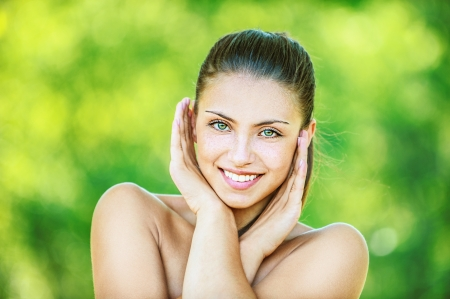 Portrait of young beautiful woman with bare shoulders crossed her arms and smilling, on green background summer nature. photo