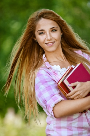 Portrait of beautiful smiling young woman with books, against green of summer park. Stock Photo - 13764508