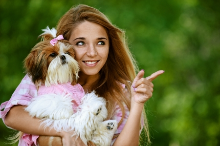 Portrait of beautiful smiling young woman with small dog, against green of summer park. photo