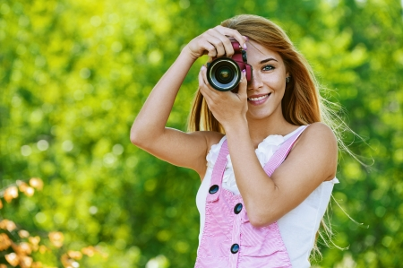 Portrait of beautiful smiling young woman with camera, against green of summer park. photo