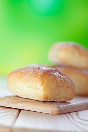 farinaceous: Wheat buns on breadboard, on background of green summer garden. Stock Photo