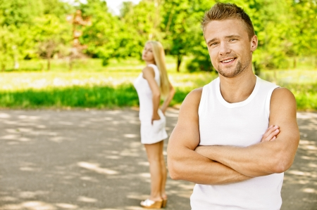 Young beautiful smiling couple dressed in white, against green of summer park. photo