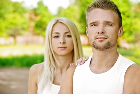 Young beautiful couple dressed in white close up, against green of summer park. photo