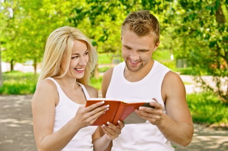 Young beautiful smiling couple dressed in white reading book, against green of summer park. photo