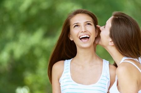 Fille raconte son bavardage ami, sur un fond vert du parc l'été.