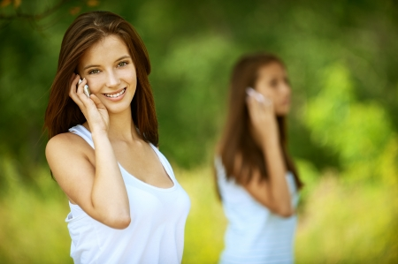 Two pretty girls talking on cell phone, against green of summer park. photo