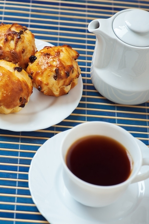 Small muffins on plate, jug of milk and cup of tea on blue bamboo table cloth. photo