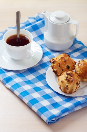 Small muffins on plate, jug of milk and cup of coffee on blue table cloth. photo