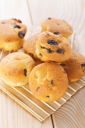 viands: Small muffins with raisins on bamboo table cloth.
