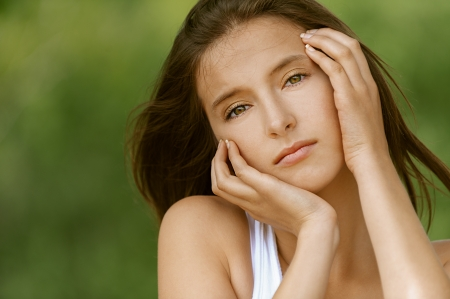 Portrait of beautiful young woman, against green of summer park. Stock Photo - 14259524