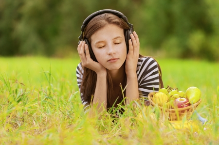 Beautiful young woman with eyes closed, lie on grass and listening to music through headphones, against green of summer park. photo
