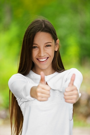 Smiling teenage girl picks up big thumbs up, against green of summer park. photo