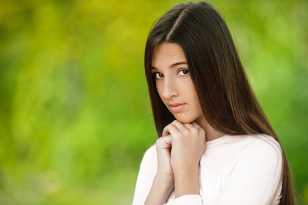 Beautiful teenage girl, against green of summer park. Stock Photo - 14259519